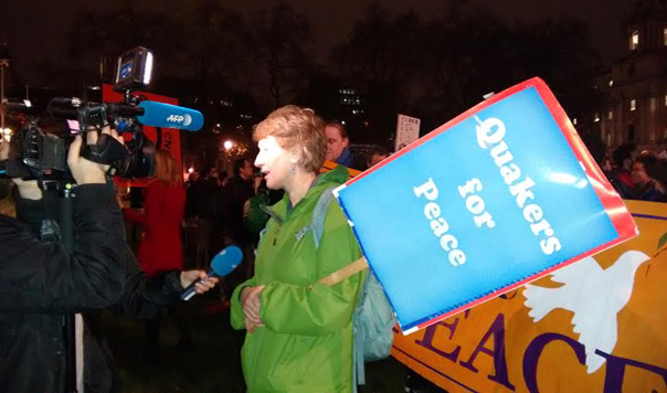 "Woman with ""Quakers for Peace"" placard talks to television crew"
