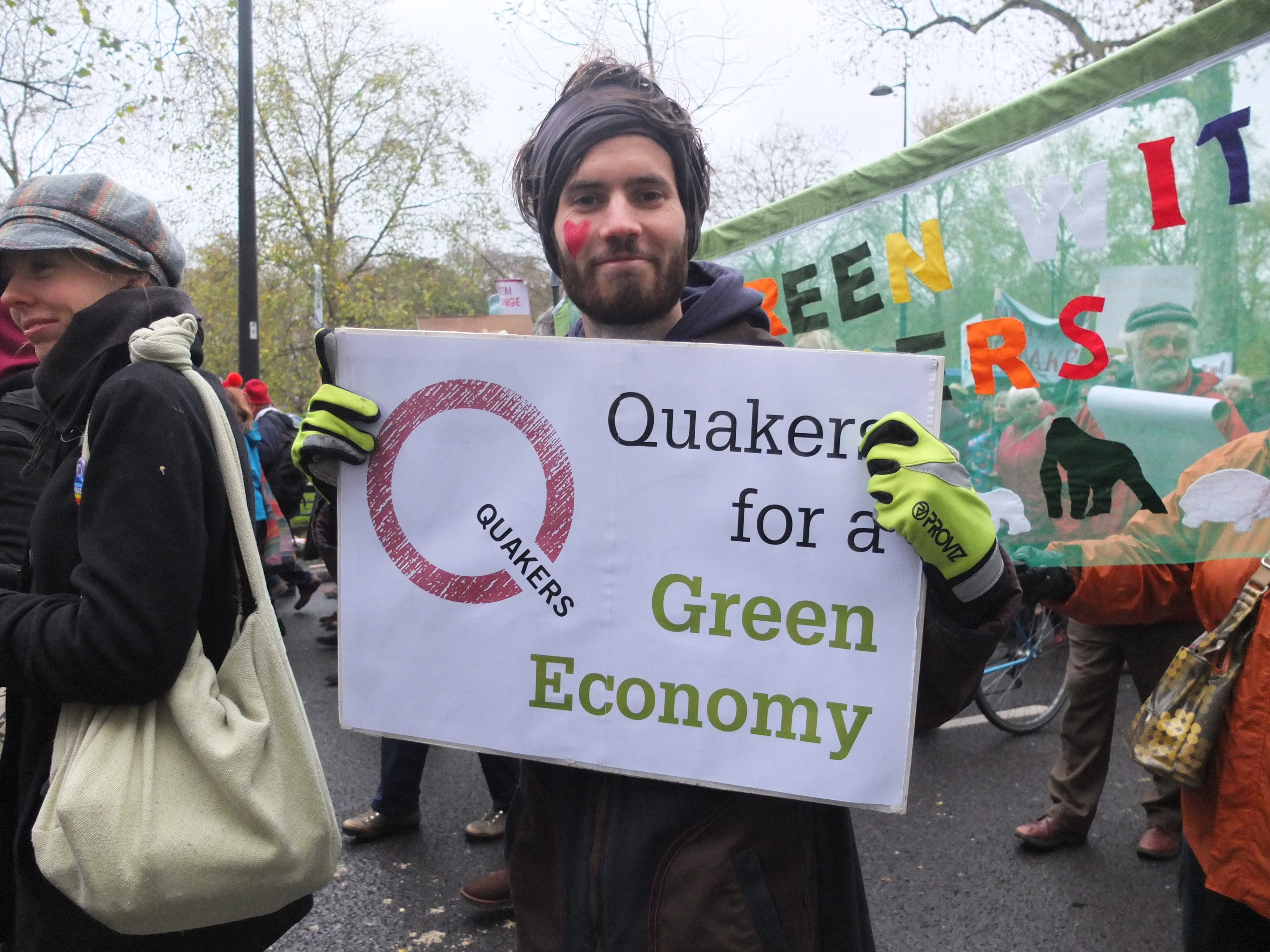 young man with facepaint holds a banner saying Quakers for a green economy