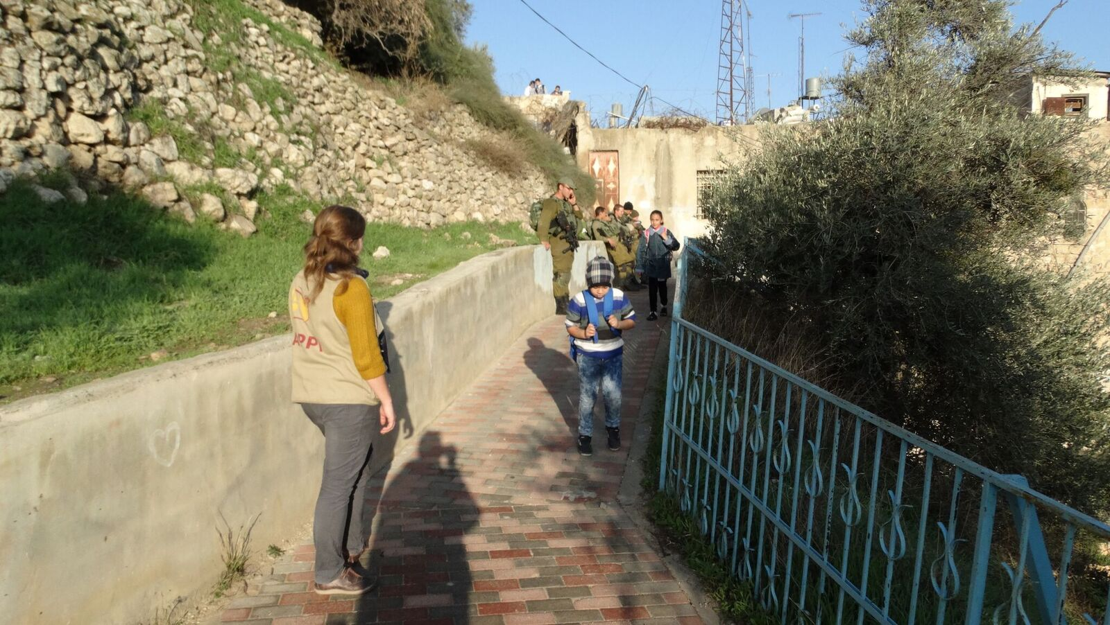 Palestinian schoolchildren encouraged by human rights monitors, pass by Israeli soldiers