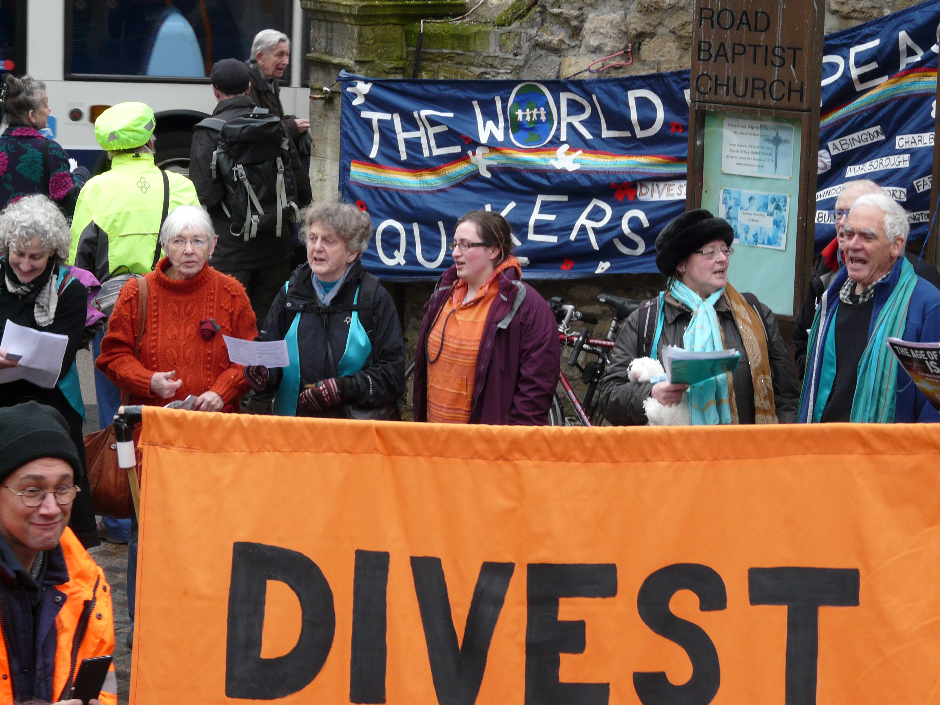 a dozen Quakers around huge organe banner saying Divest