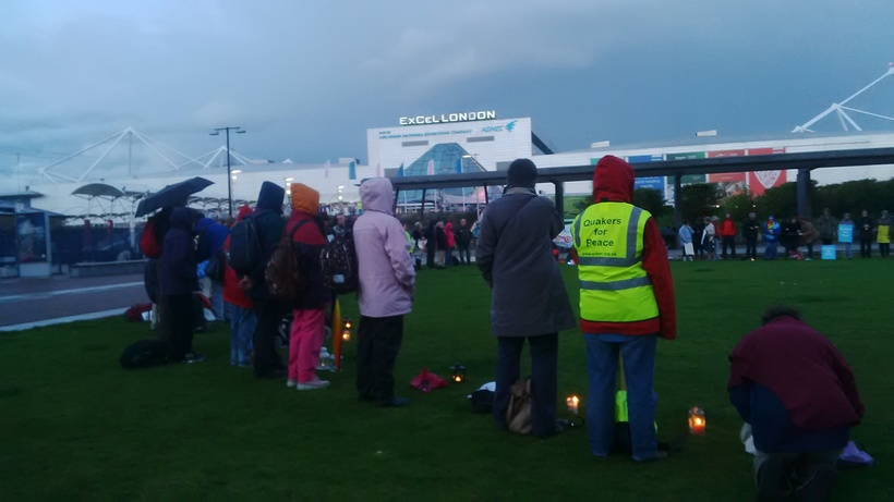 A circle of people of many faiths and none stand in a circle by candlelight outside the DSEI Arms Fair at London's Excel Centre.