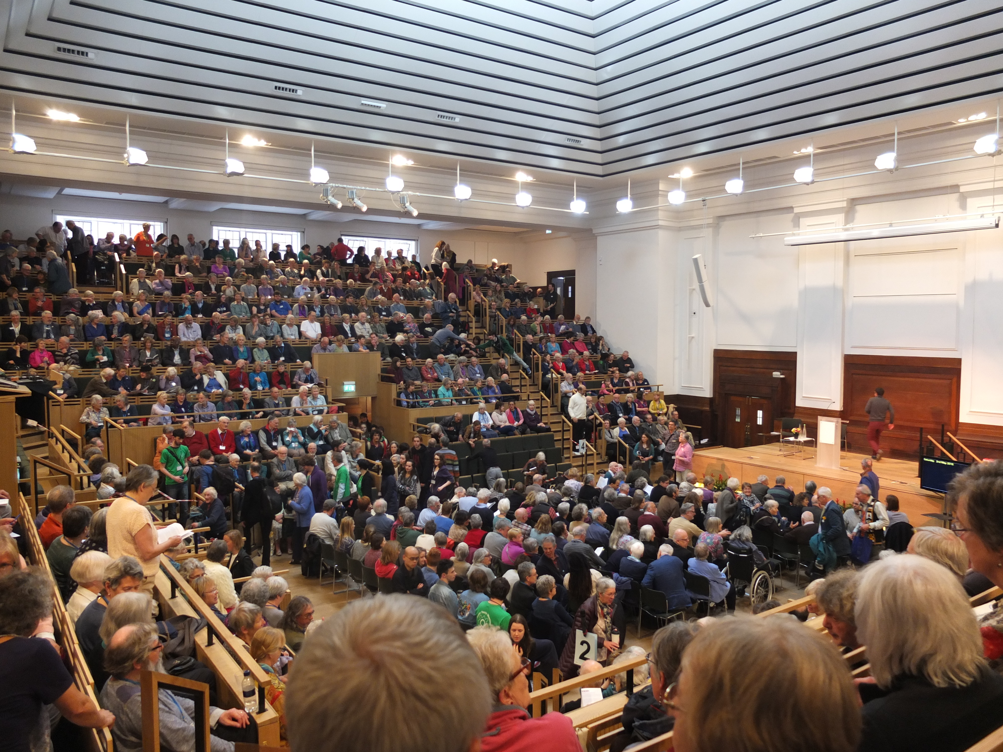 Around 1000 Quakers seated in the tiered large meeting house waiting for the swarthmore lecture to begin