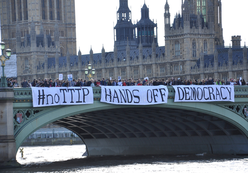 campaigners cross Westminster Bridge where a banner says No to TTiP, hands off democracy
