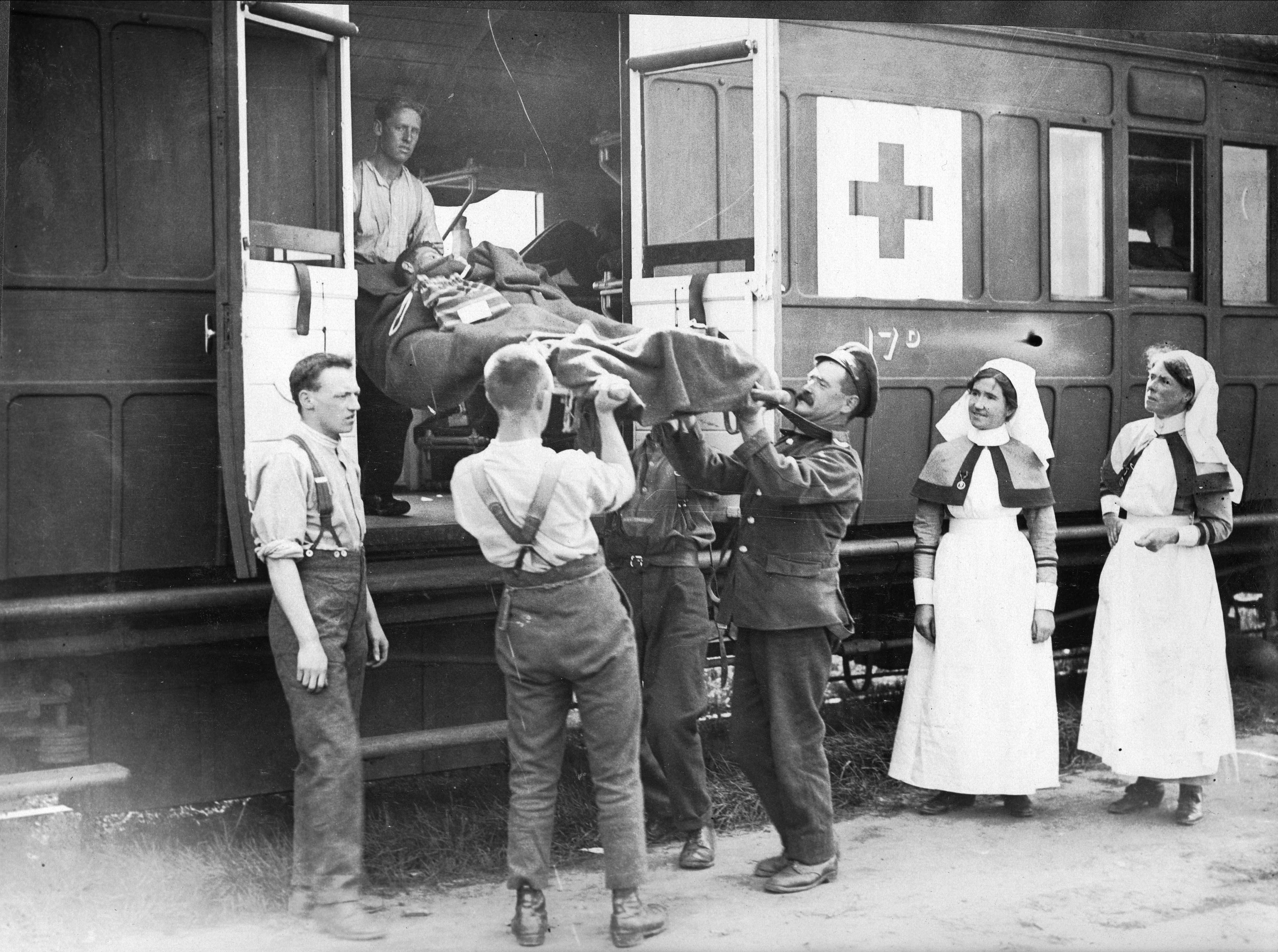 A wounded soldier on a stretcher is loaded on to train 17 by men and women in the friends ambulance unit