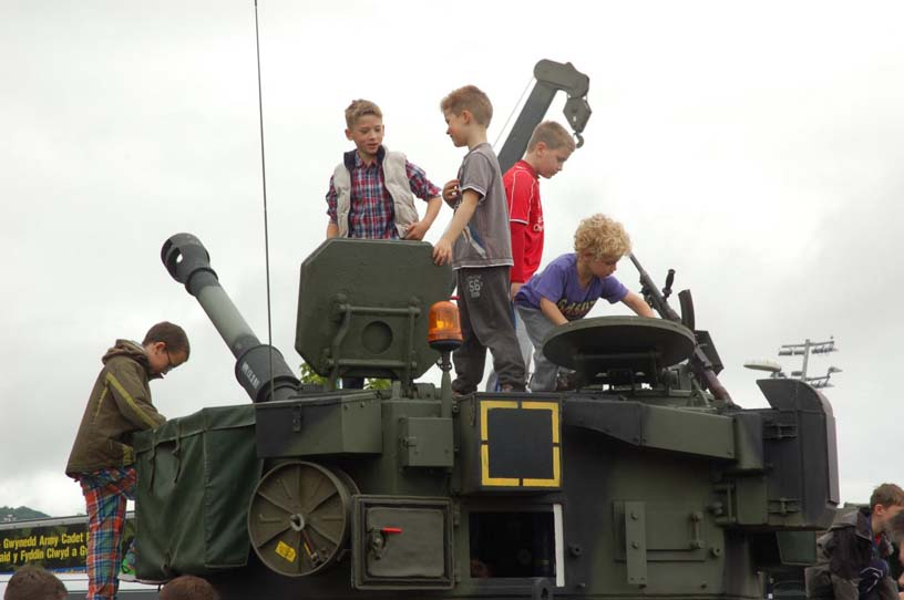 Children climbing over military tank