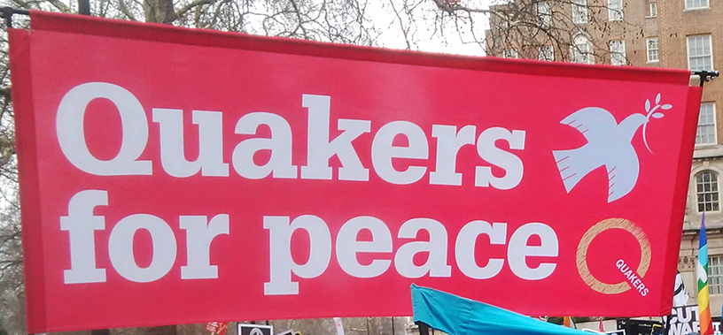 Brilliant pink banner says Quakers for peace