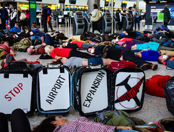 people lying on the ground pretending to be dead. Sign reads stop airport expansion stay grounded.
