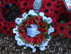 "A wreath of red and white poppies stating ""In memory of all who have suffered in all wars"""