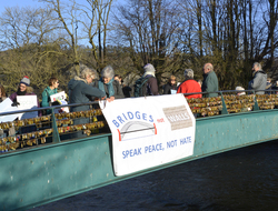Quakers in Bakewell on a bridge with a banner saying 'bridges not walls'