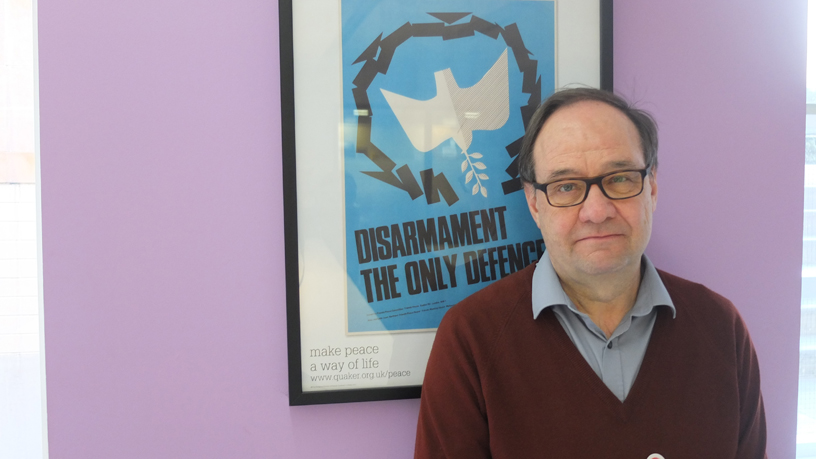 Tim Wallis by a poster which says Disarmament the only defence