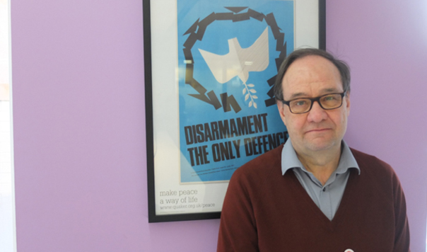 Tim Wallis by poster which says Disarmament the only defence
