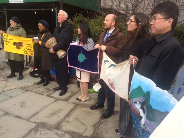 In a vigil, standing outside the UN, seven people with banners against nuclear weapons