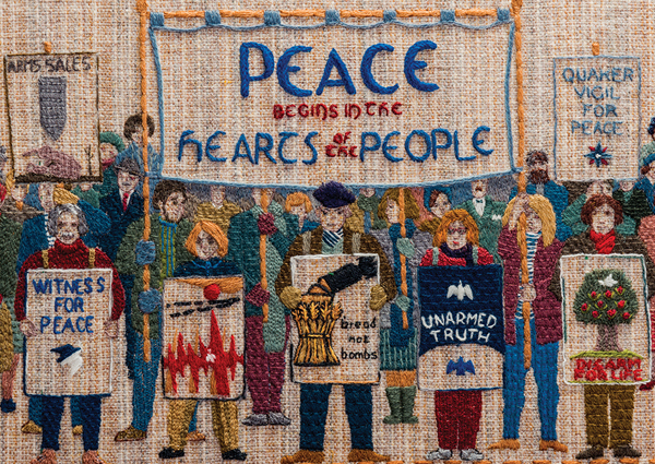 'Peace begins in the hearts of the people' section of the Quaker Tapestry with different people holding historic Quaker posters