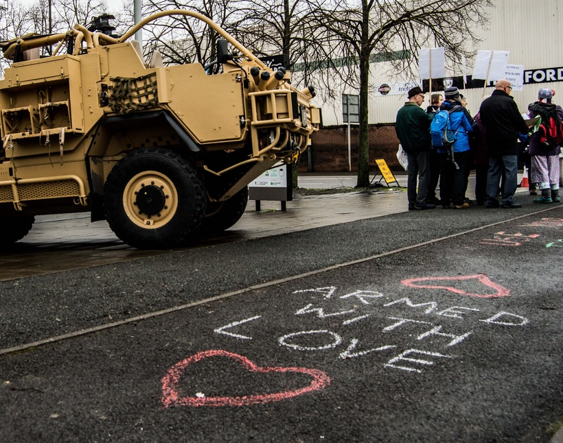 "Protesters stand outside the arms expo in Hereford next to their words ""Armed with Love"" chalked on the floor"