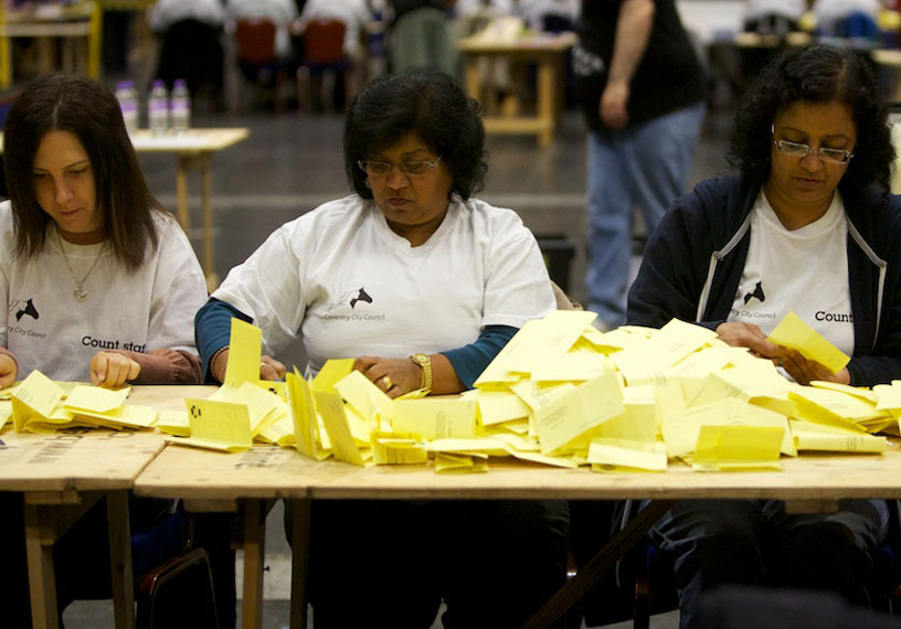 Three women seated at table counting hundreds of yellow ballot papers