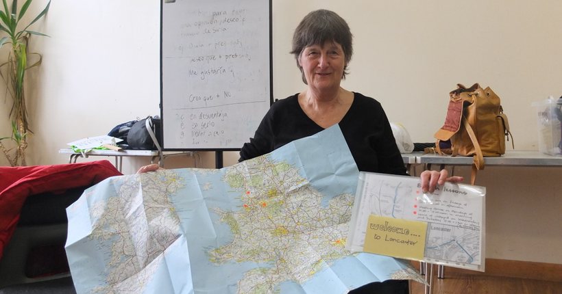 A woman holding up a map of the UK and Ireland and a pack entitled 'Welcome to Lancaster'