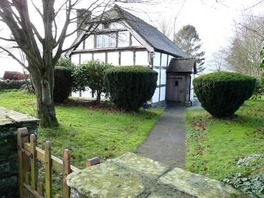 White timber framed house with a garden path leading to its front porch