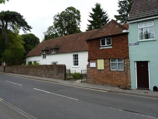 Small terraced brick cottage facing a main road.