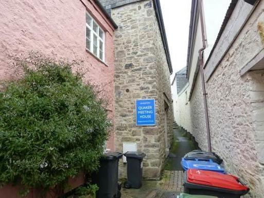 Stone house partially viewable from narrow alleyway, blue sign reads Quaker Meeting House.