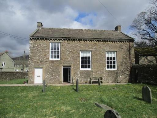 Short, squat stone building with large windows, situated within a burial ground.