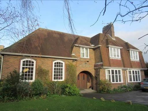 Large brick house with wide white windows and archway over double entrance doors.