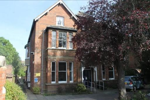 Three storey brick semi-detached house, its front door and entry slope are shaded by large trees.