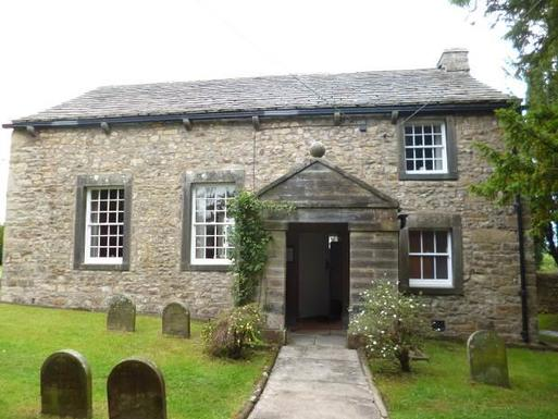 One storey stone cottage with flowers around the door is located within a Quaker burial ground.