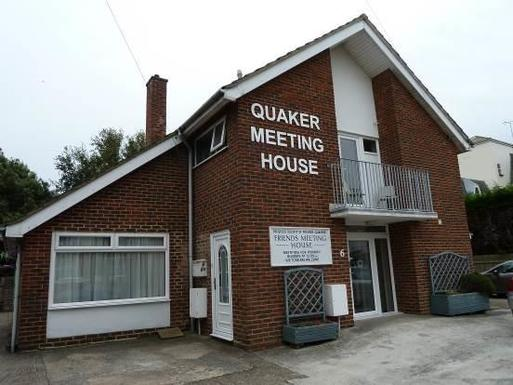 Large brick house with high roof peak and large white lettering reading 'Quaker Meeting House'.