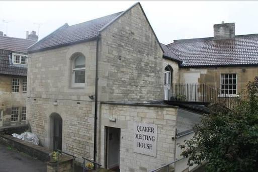 Stone townhouse with rounded windows and large 'Quaker Meeting House' sign.