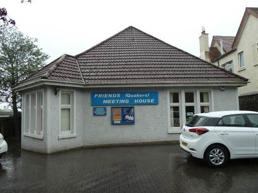 White bungalow within a car park with noticeboards and blue 'Friends (Quakers) Meeting House' sign affixed to the building.