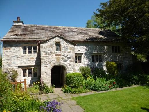 Large stone house with arched entryway and wide cottage gardens.