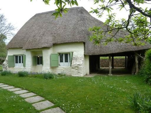 Small cottage with large thatched roof and three windows flanked by light-green shutters.