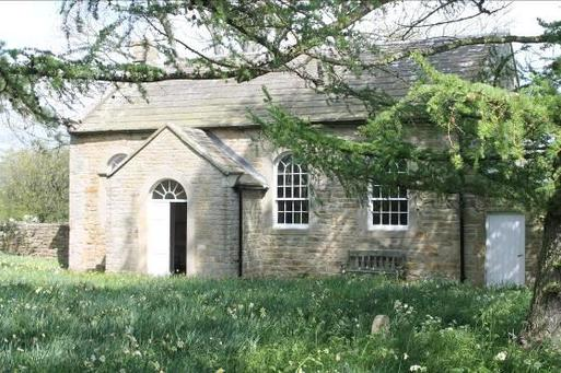 One storey stone building with large arched windows and entryway porch, set within large meadow gardens.
