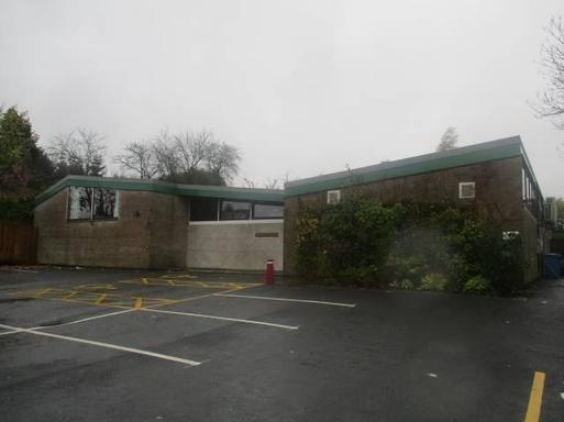 Large wide brick building with asymmetric windows and diagonal flat roof, set within a large car park.