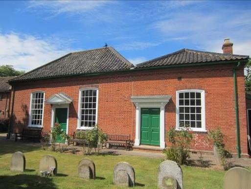 Small redbrick building with long white windows and dual large green doors, set within a small Quaker burial ground.