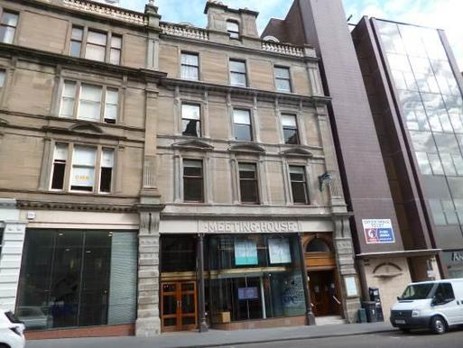 Four storey stone townhouse facing onto city centre street, 'Meeting House' carved above glass front entrance.