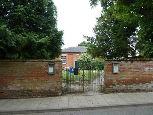 Short brick building set in large gardens is viewed through metal gate set in tall brick boundary wall.