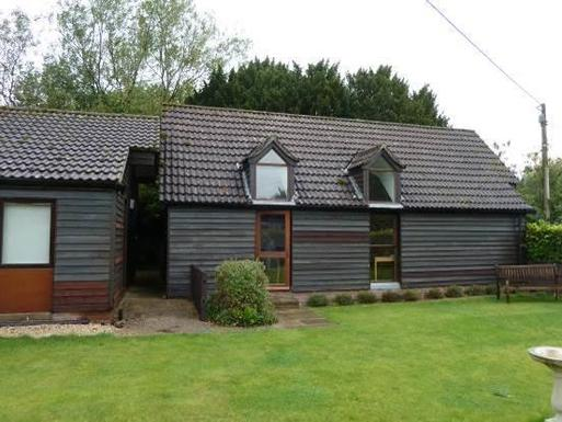 Grey wooden building with dormer windows, set within garden grounds.