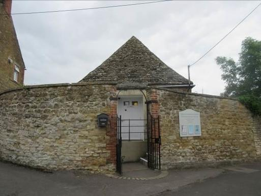 Small old stone building is nearly completely obscured by a high stone boundary wall, a white front door is visible through the entrance gate.