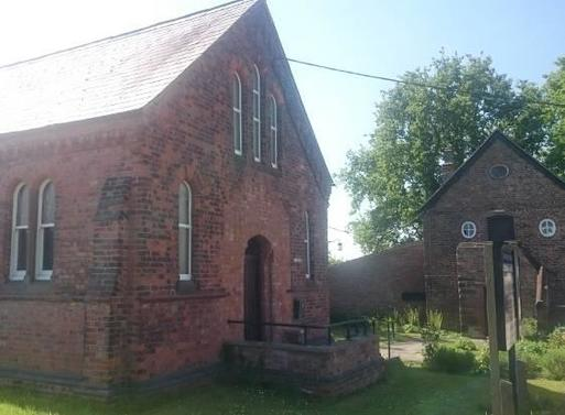 Old redbrick chapel with high roof peak within large garden grounds.