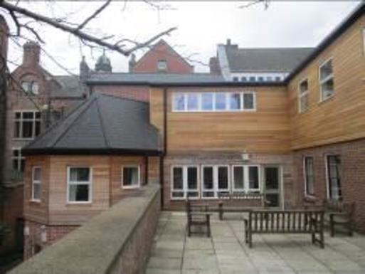 Extended building with courtyard and balcony with modern wood panelling covering old brickwork.