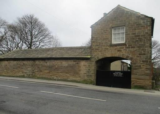 Stone meeting house visible from the street through a large gated archway.