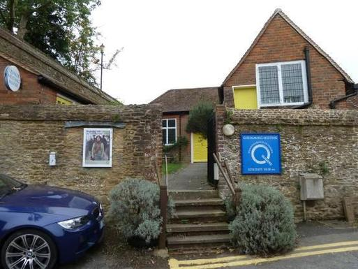 Stone cottage with yellow doors flanked by high stone walls, a large blue Q Quaker sign is attached to the right boundary wall.