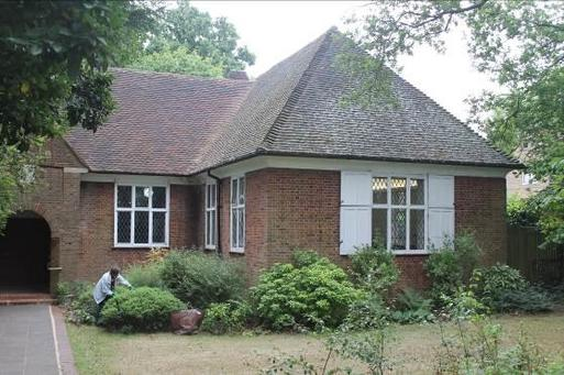Brick bungalow with white shuttered windows is within pleasant gardens.
