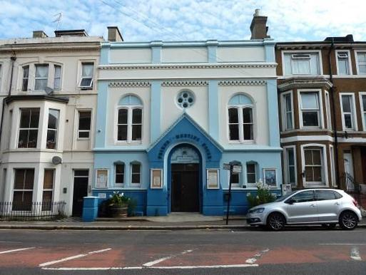 Light blue terraced building with white decorative elements and a large dark blue entrance arch with 'Friends Meeting House' lettering.
