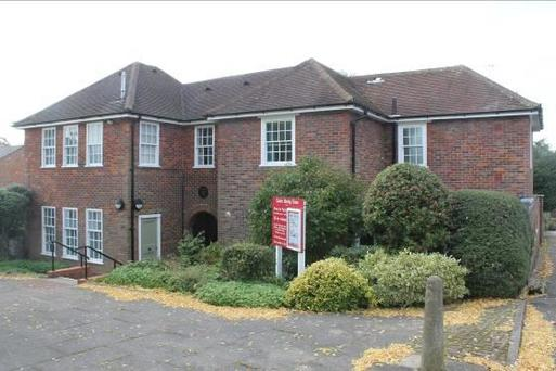 Large brick house with large windows and bright red noticeboard in its small front garden.