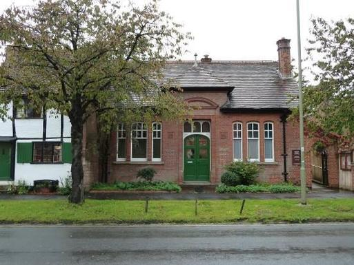One storey brick building with decorative brickwork and green front door.