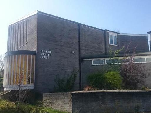Two-storey modernist grey brick building with large feature bay window and Quaker Meeting House white lettering.