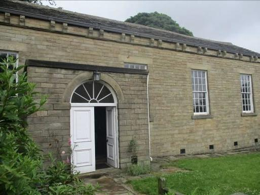 Short stone building with large windows and white entrance doors.