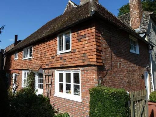 Two storey brick cottage with a low roof and decorative period features.